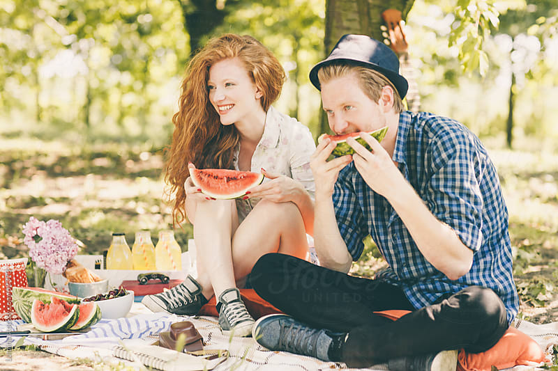 Couple Eating a Watermelon on a Picnic by Lumina for Stocksy United