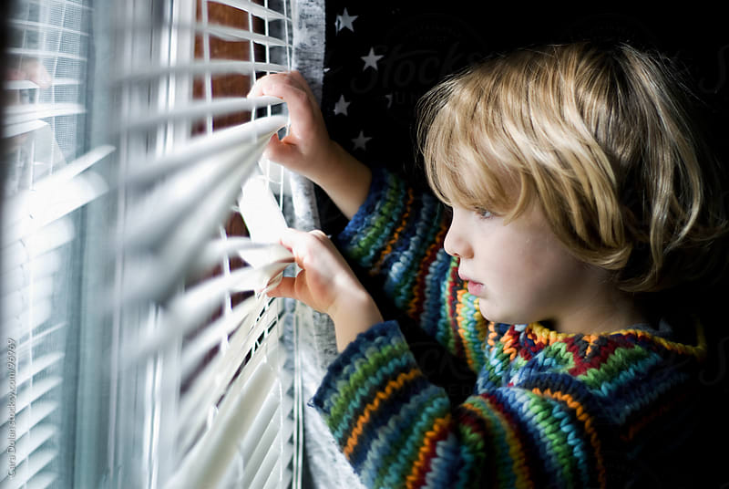 Young child peeks through blinds to look out a window by Cara Dolan for Stocksy United