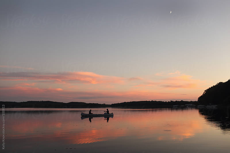 canoe on a lake at sunset by Kelly Knox for Stocksy United