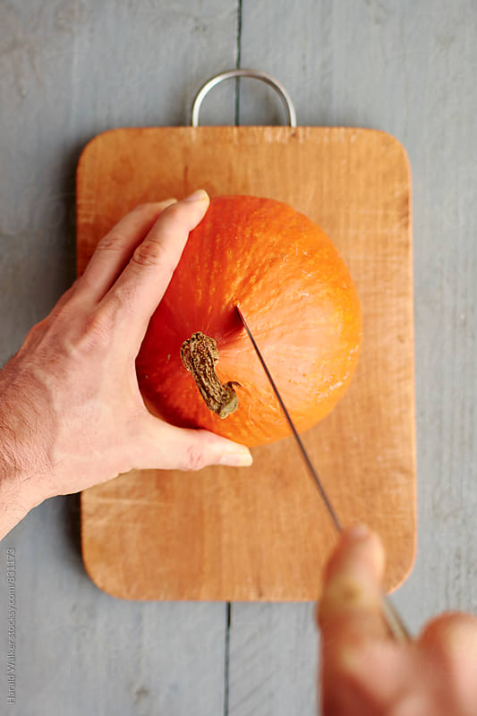 Cutting a red kuri squash by Harald Walker for Stocksy United