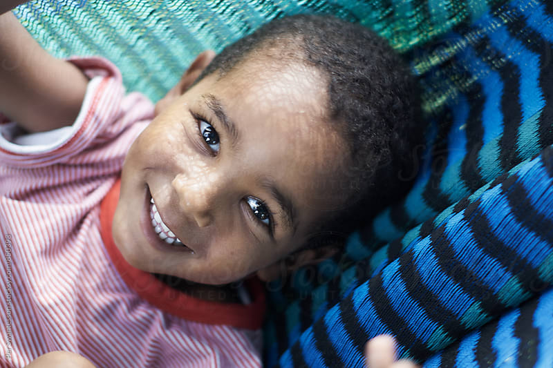 Happy young boy in a hammock by Per Swantesson for Stocksy United