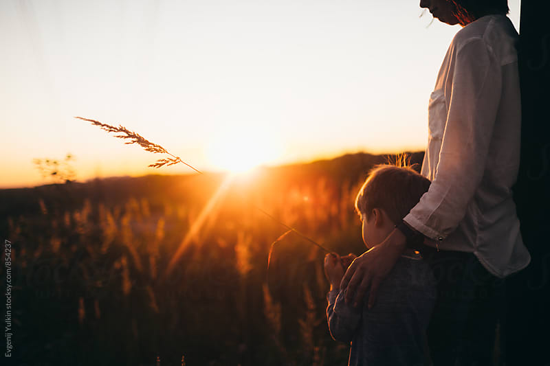 Mother and son watching the sunset by Evgenij Yulkin for Stocksy United