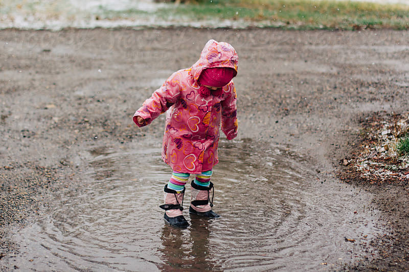 Toddler girl in pink raincoat splashing in puddle by Jessica Byrum for Stocksy United