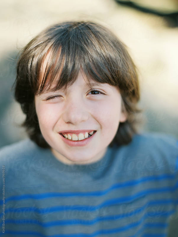 boy looking in the camera with a smile by Kirill Bordon photography for Stocksy United