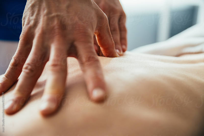 Male hands giving a massage on someones back by Inuk Studio for Stocksy United