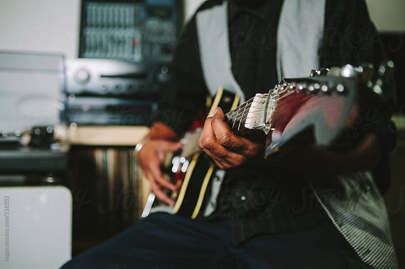 Musician's hands playing a guitar in a home studio by kkgas for Stocksy United