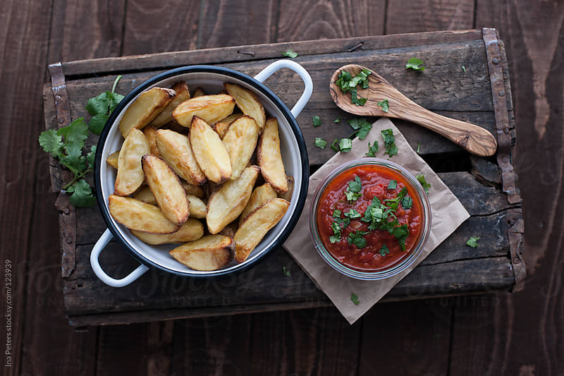 Food: Patatas Bravas, baked potatoes with a spicy tomato sauce g by Ina Peters for Stocksy United