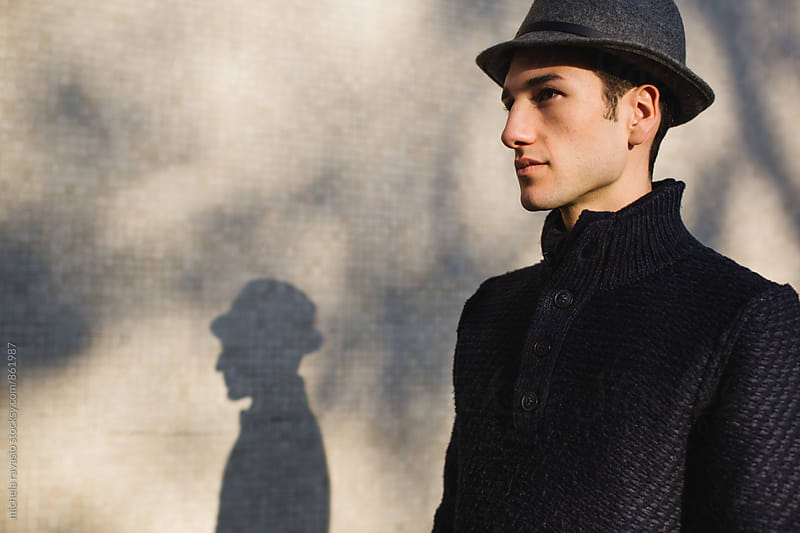 Young man walking down the street illuminated by sunlight by michela ravasio for Stocksy United