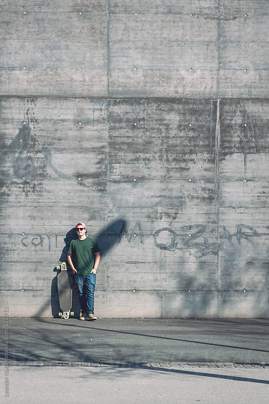 Teenager with longboard in front of a wall by Leander Nardin for Stocksy United