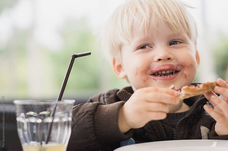 Happy toddler eating, with face full of jam by Per Swantesson for Stocksy United