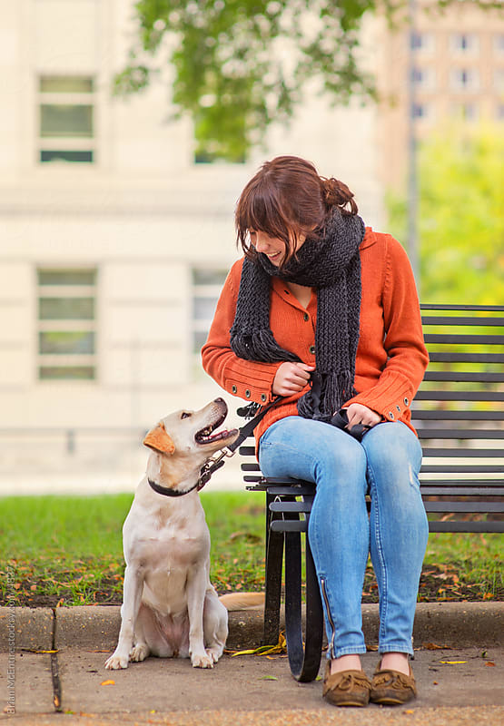 Retro styled woman sitting with Dog on Park Bench by Brian McEntire for Stocksy United