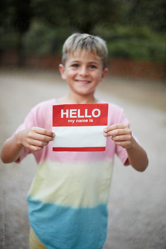 Young smiling boy holding a napkin with the words hello my name is by Miquel Llonch for Stocksy United