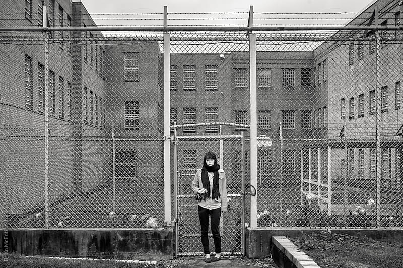 Decay Tourism: Young Woman with Camera Outside Barbed Wire Facil by Brian McEntire for Stocksy United