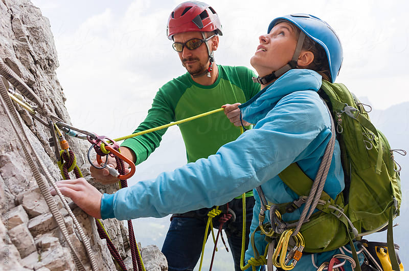 Rock climbers on the cliff regroup and check their climbing equipment by RG&B Images for Stocksy United