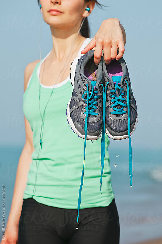 Young runner showing wet running shoes after beach workout. She is listening music. by BONNINSTUDIO for Stocksy United