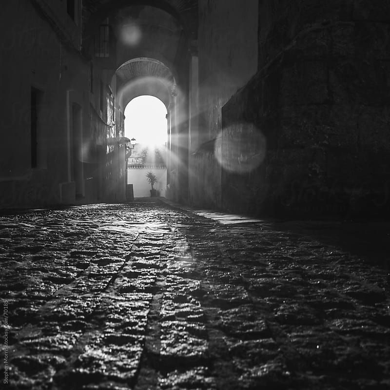 Sun Shining through Arches in Spanish Alleyway by Stephen Morris for Stocksy United