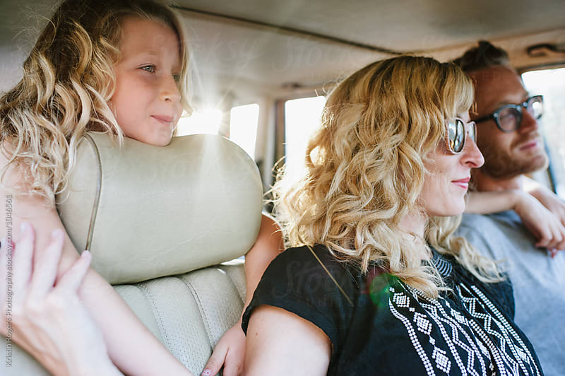 Young girl sitting in back of car with profile at golden hour by Kristin Rogers Photography for Stocksy United