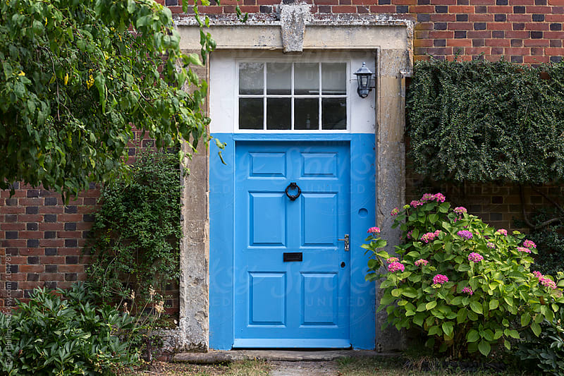 An old  blue door with a stone surround against a brick wall by Paul Phillips for Stocksy United