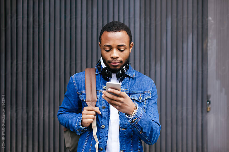 Portrait of an african american man using his phone outside. by BONNINSTUDIO for Stocksy United