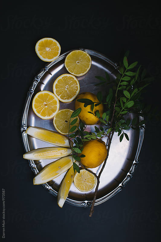 Sliced lemons on a silver tray. by Darren Muir for Stocksy United
