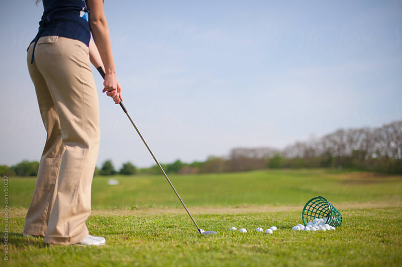 Female Golfer Addresses Ball On Driving Range Grass Tee by Brian McEntire for Stocksy United