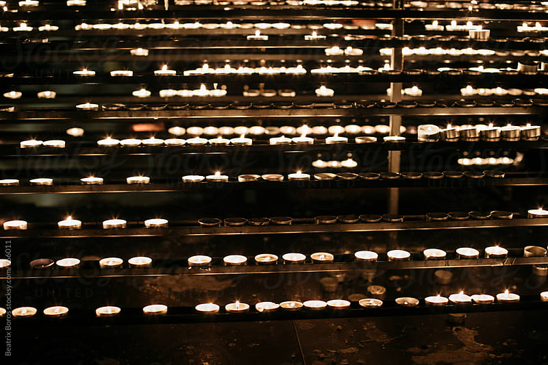 Candles arranged in a row in a church by Beatrix Boros for Stocksy United