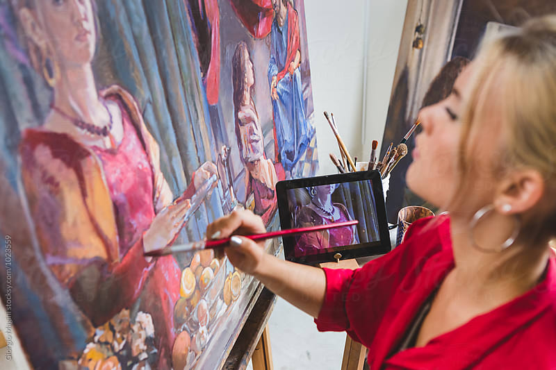 Female Artist Paints while Watching at the Tablet, Technology Helps by Giorgio Magini for Stocksy United