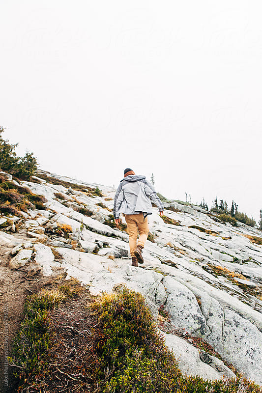 Young Man Walking Up Granite Face Of Foggy Mountain by Luke Mattson for Stocksy United