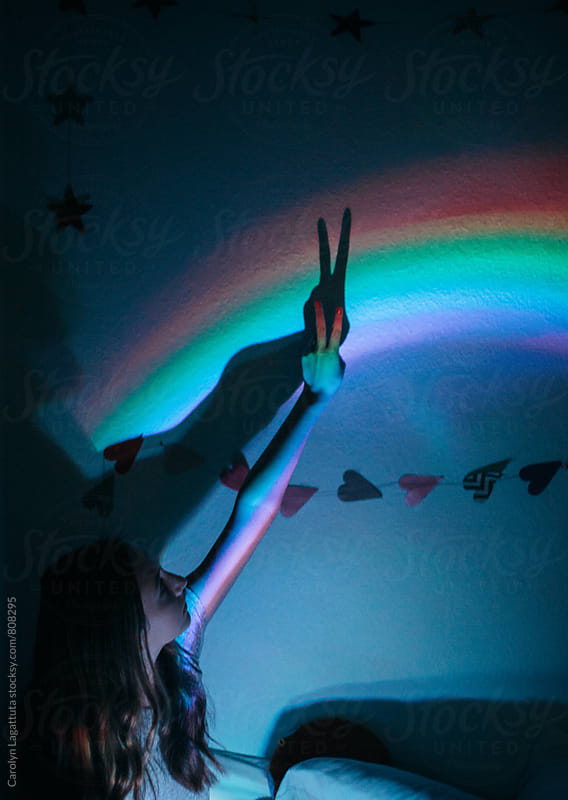 Teenage girl holding her hand up in the shape of a peace sign against a rainbow by Carolyn Lagattuta for Stocksy United