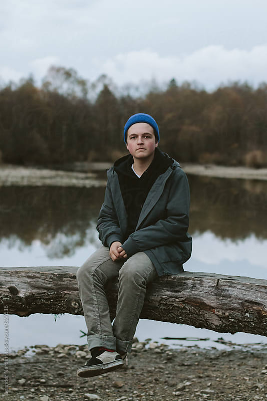 portrait of a young male teenager sitting on a wooden bridge  by Leander Nardin for Stocksy United