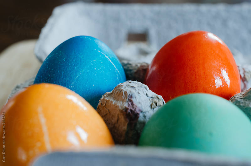 Easter eggs dyed red, blue, orange and green by Cara Dolan for Stocksy United