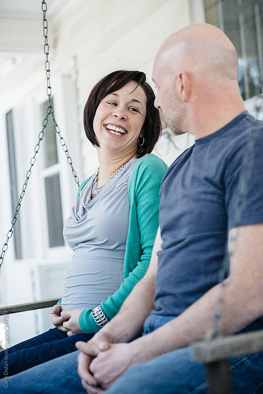 Pregnant woman and her husband laugh talk on their front porch at home by Cara Dolan for Stocksy United