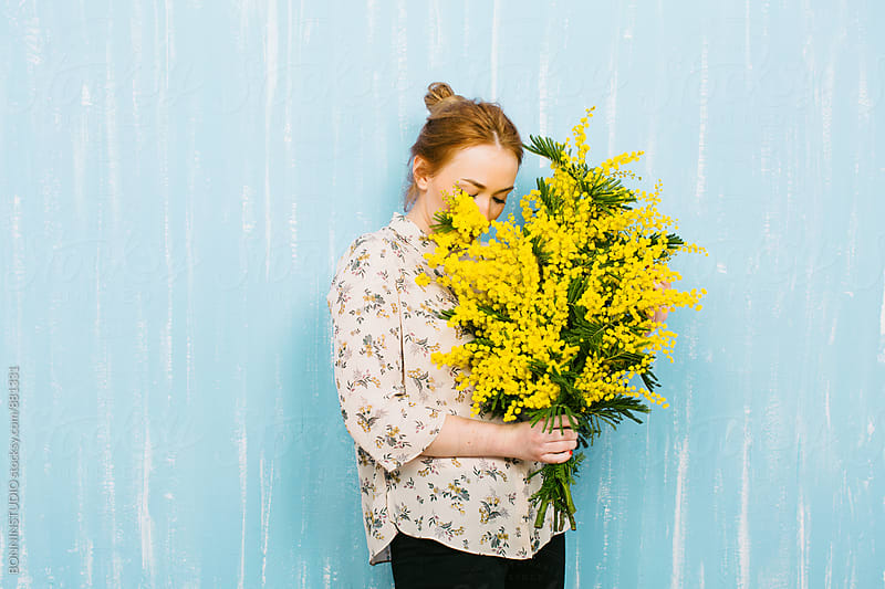 Ginger woman smelling a bouquet of yellow flowers. by BONNINSTUDIO for Stocksy United