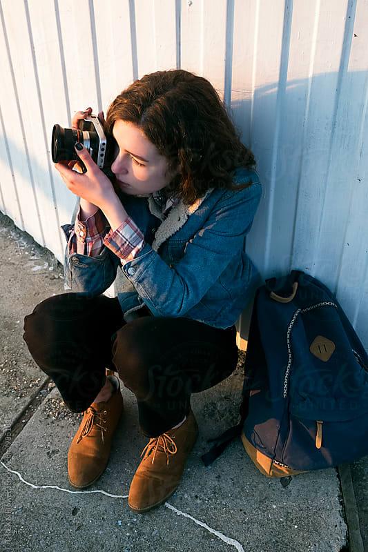 Young brunette taking shot using film camera by Danil Nevsky for Stocksy United