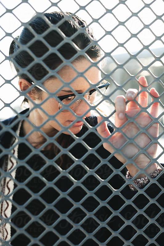 Portrait of a young hipster woman taken through a fence. by BONNINSTUDIO for Stocksy United