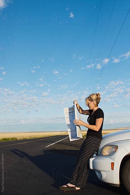 woman sits on car looking at map by Tana Teel for Stocksy United