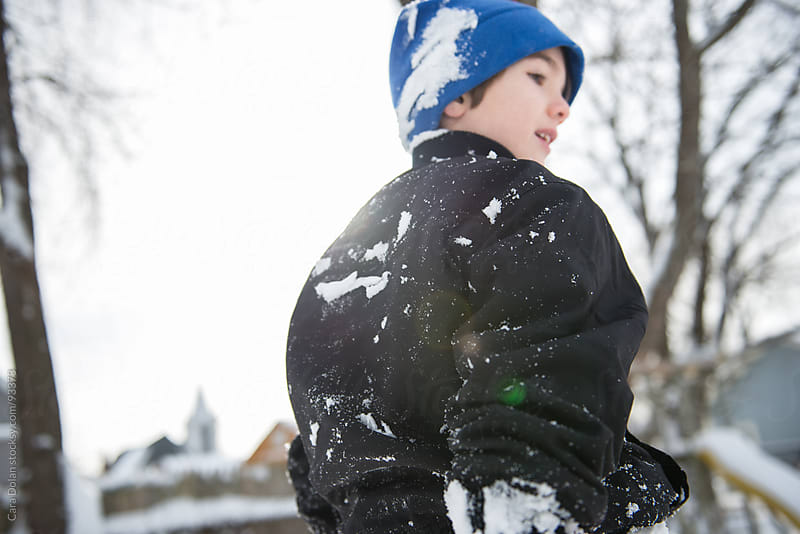 Boy in snow-covered winter clothes walks in his back yard  by Cara Dolan for Stocksy United