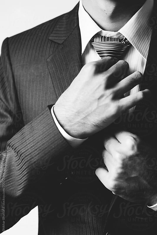 Details of a man adjusting his tie. by Shikhar Bhattarai for Stocksy United