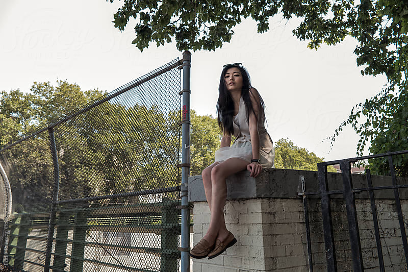 Pretty young woman sitting on top of ledge by Eddie Pearson for Stocksy United