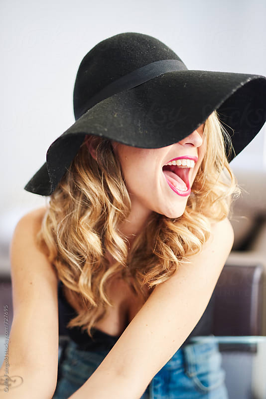 smiling blonde woman with black hat by Guille Faingold for Stocksy United