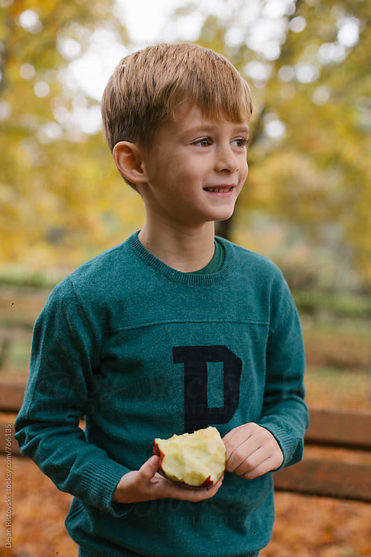 Child eating apple in the park. by Dejan Ristovski for Stocksy United