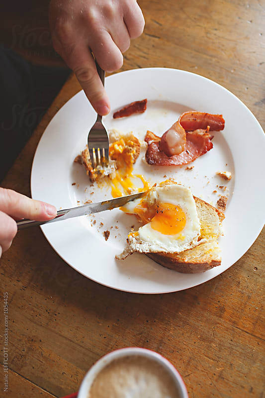 Fried egg, bacon, toast and coffee for breakfast by Natalie JEFFCOTT for Stocksy United