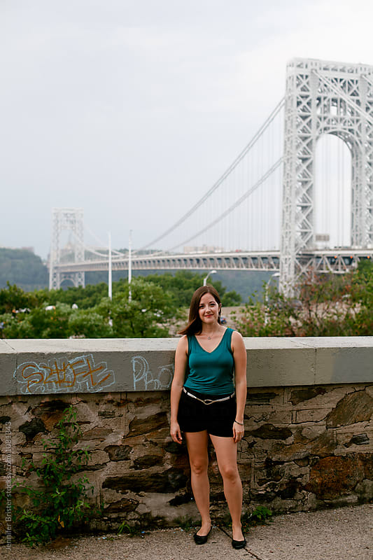 Woman standing in front of bridge by Jennifer Brister for Stocksy United
