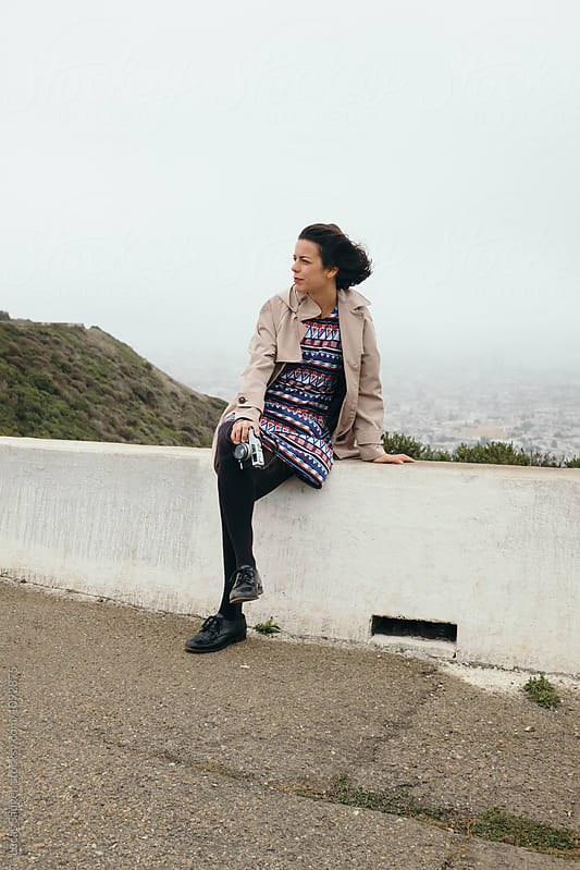 Pensive brunette traveler with vintage camera against of cityscape in fog by Lucas Saugen for Stocksy United