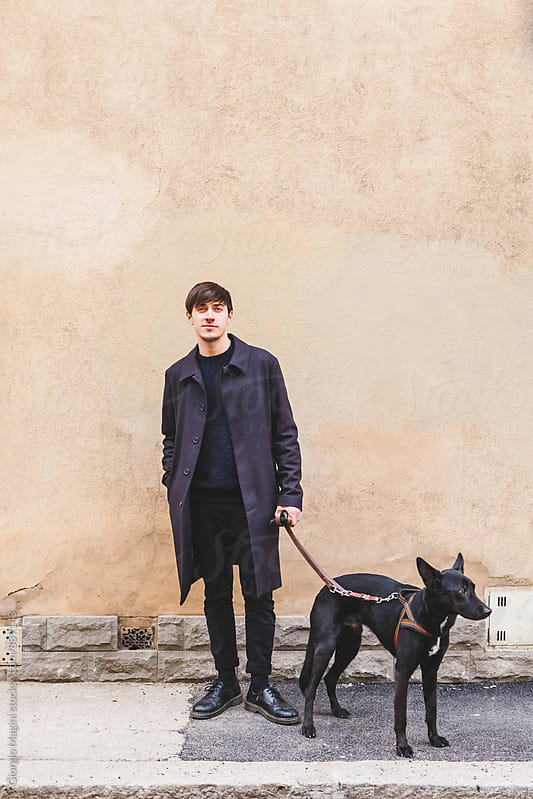 Young Man with Black Dog Standing on a Sidewalk by Giorgio Magini for Stocksy United