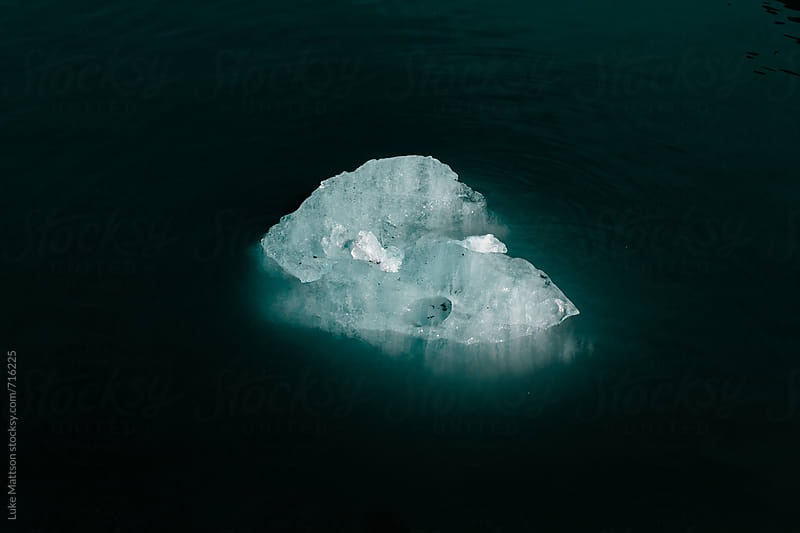 A Ghostly Piece Of Glacial Ice Floats In The Dark Blue Waters Of Aialik Bay by Luke Mattson for Stocksy United