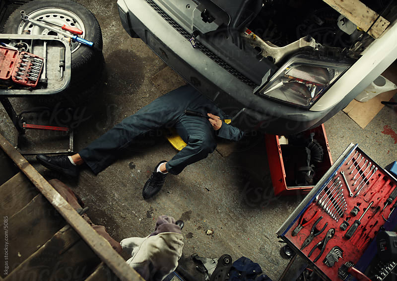 Mechanic under vehicle. by kkgas for Stocksy United