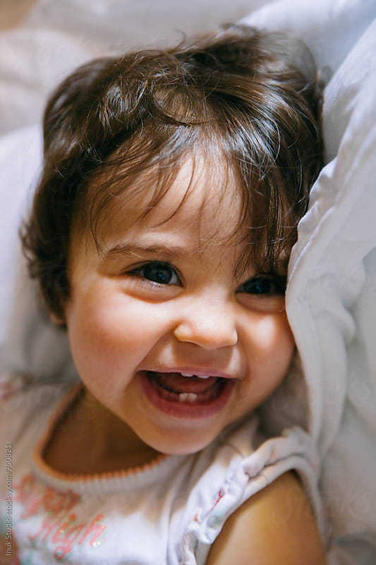 Adorable baby girl portrait laughing lying on a bed by Inuk Studio for Stocksy United