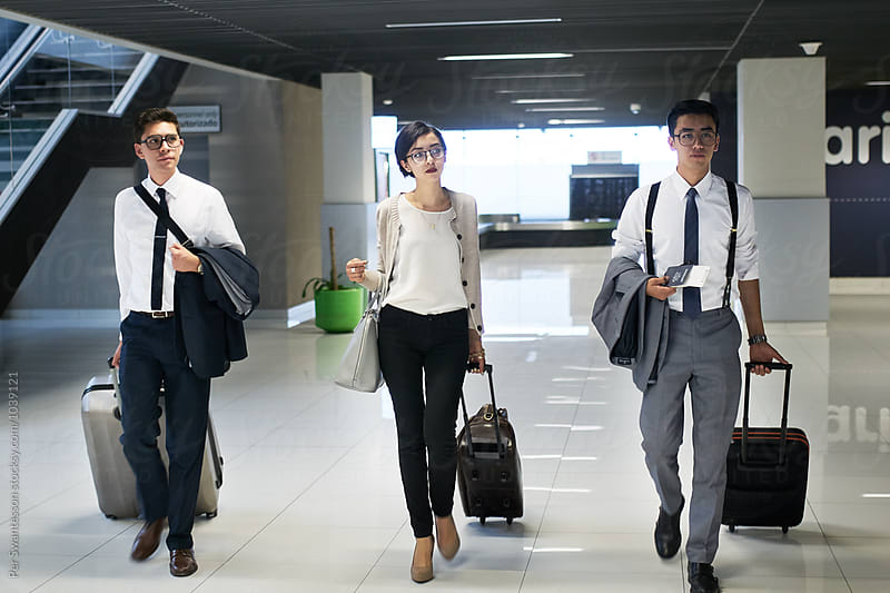 Coworkers walking with suitcases at the airport by Per Swantesson for Stocksy United