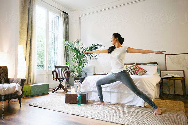 Young asian woman practicing yoga exercises at home. by BONNINSTUDIO for Stocksy United